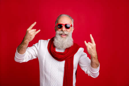 Modern santa character aged man showing horns heavy metal fan wear sun specs knitted clothes isolated red background 写真素材