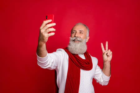 Portrait of his he nice attractive cheerful cheery glad positive gray-haired man taking making selfie showing v-sign isolated over bright vivid shine red background