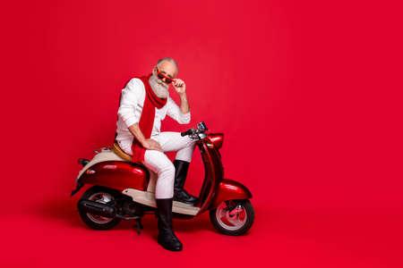 Flirty Großvater Santa Mann sitzt auf Retro-Moped tragen Pullover und Hose isoliert auf rotem Hintergrund