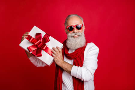 Cool aged santa like man came meeting newyear with large giftbox wear sun specs knitted jumper isolated red background