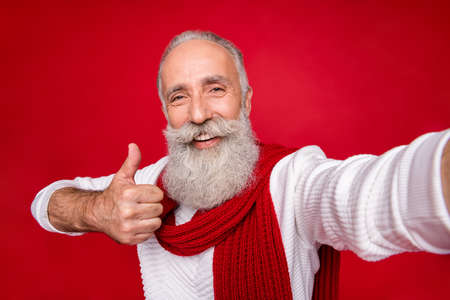 Self-portrait of his he nice attractive confident content cheerful cheery gray-haired man grandpa giving thumbup ad advert advice isolated over bright vivid shine red background