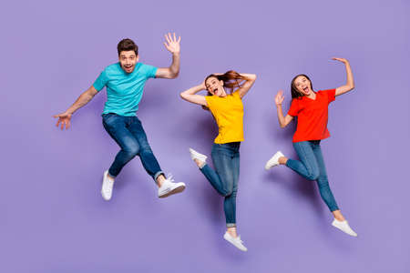 Full length size body photo of two beautiful carefree cheerful excited ladies and one comic funny in blue t-shirt guy waving hand saying hello isolated violet background Stok Fotoğraf