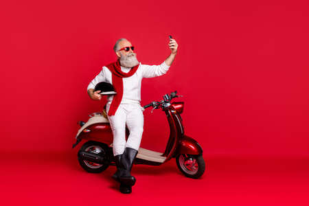 Portrait of his he nice attractive stylish trendy confident content gray-haired man holding in hands phone taking making selfie isolated over bright vivid shine red background