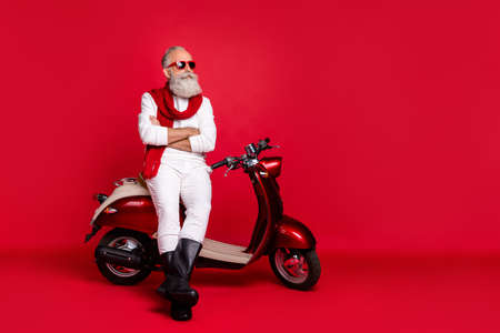 Aged macho man sitting on retro moped with crossed arms wear jumper and trousers isolated red background Stok Fotoğraf