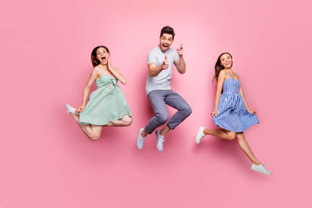 Full length photo of cheerful youngsters jump show choice with index finger, wear striped t-shirt pants trousers isolated over pink background