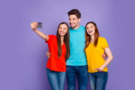 Portrait of nice attractive lovely friendly cheerful cheery glad guys wearing colorful t-shirts jeans taking making selfie having fun blog blogger isolated over violet lilac background 스톡 콘텐츠