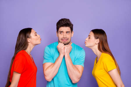 Side profile photo of two beautiful colorful ladies want to kiss one feared troubled worried handsome grimacing macho isolated violet background Stock Photo