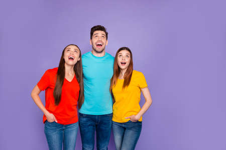 Portrait of nice attractive lovely curious cheerful cheery glad guys wearing colorful t-shirts denim waiting expecting good news looking up isolated over violet lilac background