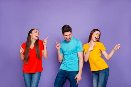 Portrait of nice attractive lovely charming cheerful cheery careless carefree, guys wearing colorful t-shirts jeans having fun disco isolated over violet lilac background
