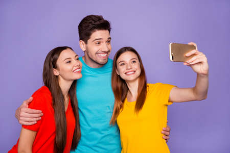 Portrait of nice attractive lovely charming cute cheerful cheery glad guys wearing colorful t-shirts taking making selfie having fun spending holiday weekend isolated over violet lilac background