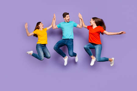 Full length body size photo of three excited glad optimistic delightful millennial generation group in blue yellow outfit having fun and good mood isolated violet background