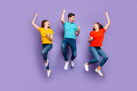 Full length size body photo of three delightful cheerful excited wild having fun group of people raising fists up isolated violet background