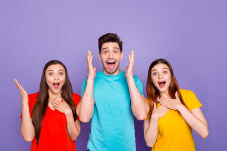 Portrait of nice-looking attractive lovely charming cheerful cheery guys wearing colorful t-shirts showing astonishment expression isolated over violet lilac background