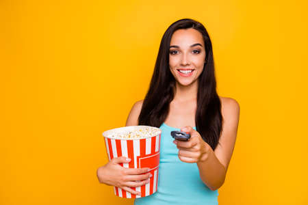 Photo of cheerful attractive charming cute nice tv watcher holding, controller with her hands pop corn pot watching comedy wearing teal tank-top isolated over vivid color background