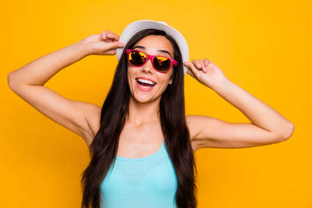 Photo of cheerful charming cute nice attractive relaxing girl wearing eyeglasses sunglass cap turquoise tank-top smiling toothily rejoicing with having gone on vacation isolated vibrant color background Stock Photo