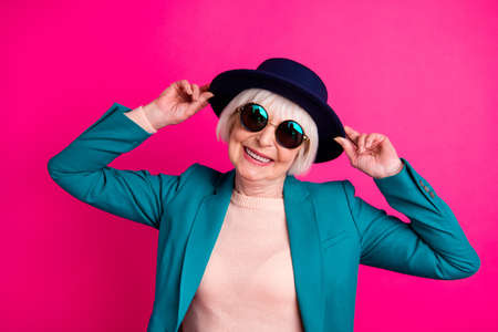 Close-up portrait of her she nice attractive fascinating well-dressed cheerful gray-haired lady touching hat enjoying weekend isolated on bright vivid shine vibrant pink fuchsia color background Imagens