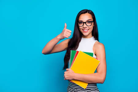 Photo of pretty lady holding study book in arms diligent student raising thumb up wear specs white tank-top and striped skirt isolated blue color background