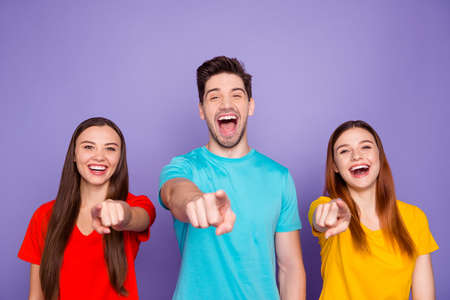 Portrait of nice-looking attractive lovely charming cheerful cheery funny guys wearing colorful t-shirts pointing at you laughing having fun isolated over violet lilac background