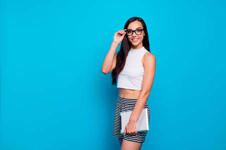 Photo of pretty lady holding e-book in arms diligent reliable student wear specs white tank-top and striped skirt isolated blue color background Stock Photo