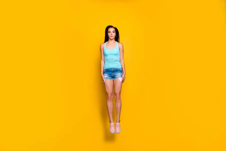 Full length body size photo of young girl stretching up straight wearing turqiouse tank-top footwear isolated over vibrant color background Stock Photo