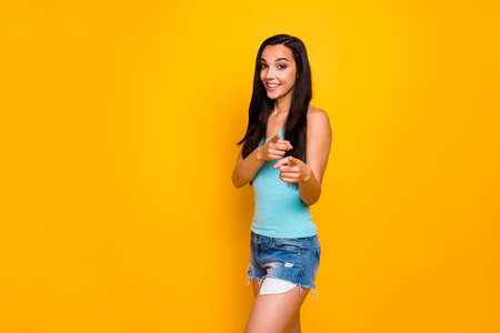 Photo of fascinating kind friendly cheerful cute girl pointing at you wearing denim shorts turquoise tank-top isolated over yellow vivid color background Stock Photo - 131542154