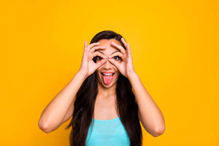 Photo of cheerful childish cute girlish woman sticking tongue out shaping binoculars with her fingers wearing turquoise tank-top isolated over yellow vibrant color background