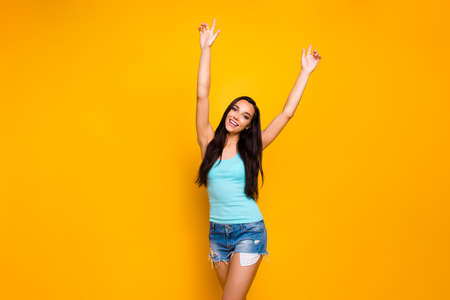 Photo of trendy beautiful cute pretty sweet young lady with her hands up excited of having won competitions wearing teal tank-top isolated over yellow bright color background
