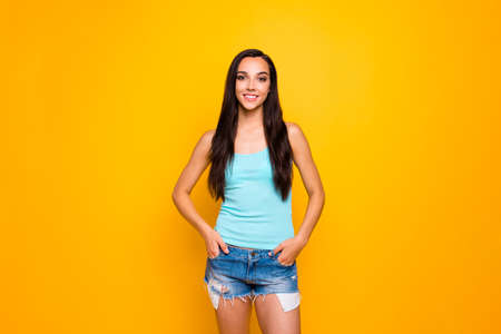 Photo of carefree sweet nice fascinating youngster holding hands in pockets of her denim shorts standing confidently wearing turquoise tank-top isolated over yellow vibrant color background