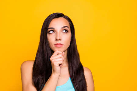 Photo of white pensive thinking guessing lady trying to recollect important knowledge looking up wearing teal tank-top isolated over yellow bright color background Stock Photo