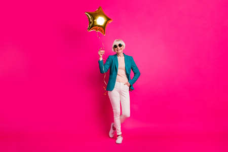 Full length body size view of nice-looking attractive well-dressed cheerful gray-haired lady holding balloon enjoying free time isolated on bright vivid shine vibrant pink fuchsia color background 写真素材