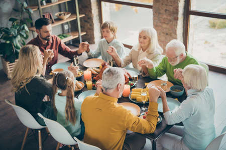 Portrait of nice lovely calm peaceful focused big full family brother sister couples eating homemade luncheon feast holding hands praying loft brick industrial style interior house indoors