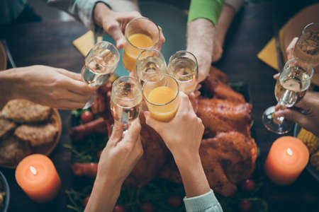 Cropped close-up view of nice big full family brother sister couples clinking glass orange juice beverage gratefulness over served table meal dishes in house restaurant catering