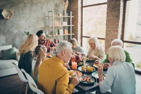 Portrait of nice lovely idyllic cheerful big full family brother sister couples eating tasty yummy meal dishes feast gratefulness autumn fall season in loft brick wood industrial style interior house