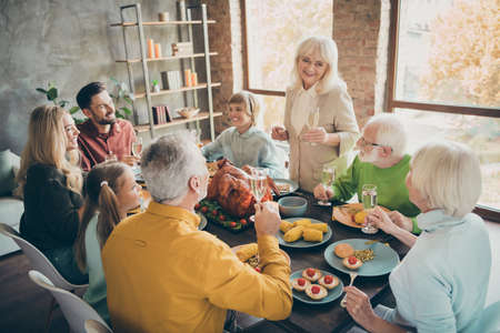 Portrait of nice cheerful big full family brother sister eating domestic brunch lunch feast generation gathering tradiotion grandma saying toast in modern loft industrial style interior house