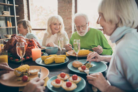 Portrait of nice lovely cheerful cheery friendly big full family eating brunch lunch delicious autumn fall season tradition generation gathering in modern loft industrial style interior house