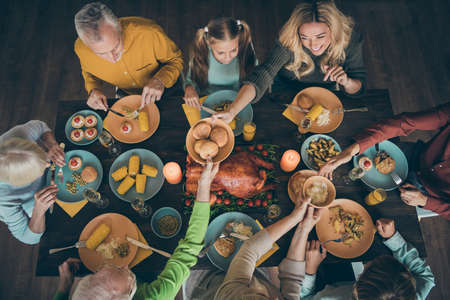 Top above high angle view of nice cheerful friendly big full family having lunch eating homemade cuisine fresh meal dishes gathering season tradition harvest in house restaurant indoors