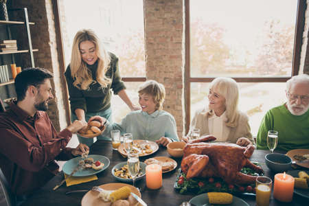 Happy thanksgiving. Photo of big family gathering sit feast meals dinner table wife giving everybody fresh baked bread multi-generation in evening living room indoors