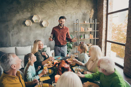 Portrait of nice cheery big full family brother sister granddaughter grandson enjoying feast tradition dad saying grateful toast congratulate daydream in modern loft industrial style interior house
