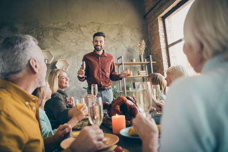 Portrait of nice cheery big full family brother sister granddaughter grandson enjoying feast generation gathering dad saying toast gratefulness congrats in modern loft industrial style interior house