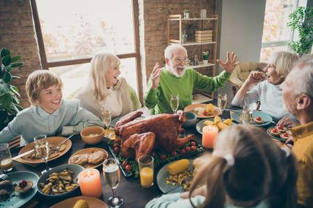 Foto de reunión familiar completa reunión sentarse platos de fiesta mesa de pollo comunicando otoño noviembre vacaciones de otoño multigeneracional en la sala de estar por la noche en el interior