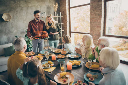 Photo of full family reunion sit feast dishes table meet big roasted turkey ovations clap hands multi-generation eight relatives annual event in living room indoors