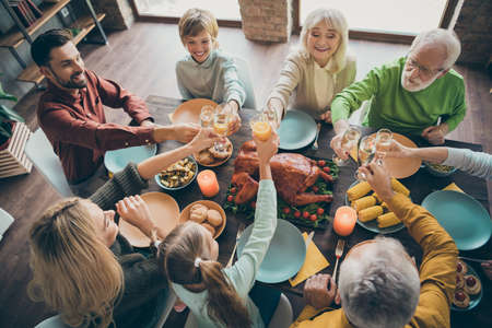Top above high angle view of nice lovely cheerful big full family brother sister couples eating tasty yummy brunch feast tradition clinking glass in loft brick industrial style interior house indoors
