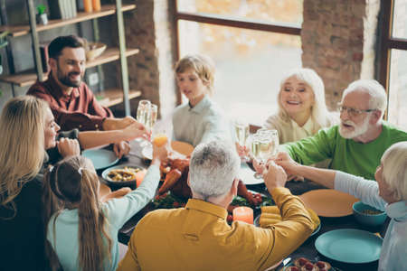 Portrait of nice lovely cheerful cheery big full family brother sister couples eating homemade brunch feast clinking glass meeting in loft brick industrial style interior house indoors