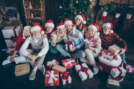 Portrait of nice lovely cheerful big full family brother sister couples in cap hat headwear sitting on floor showing v-sign christmastime day tradition decorated loft industrial style interior house Stok Fotoğraf
