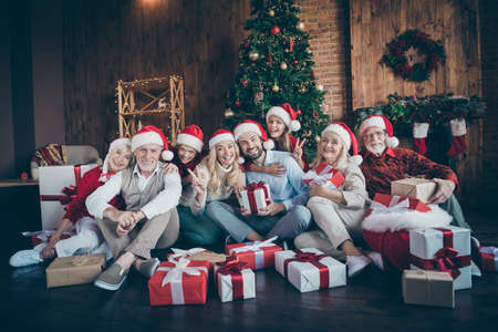Portrait of nice charming cheerful big full family brother sister couples wearing cap hat headwear sitting on floor winter tradition showing v-sign in decorated loft industrial style interior house Stok Fotoğraf