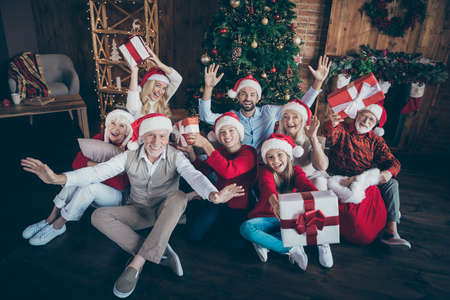 Portrait of nice lovely cheerful big full family brother sister couples wearing cap hat headwear sitting on floor holding in hands gifts waving hi hello tradition loft industrial style interior house