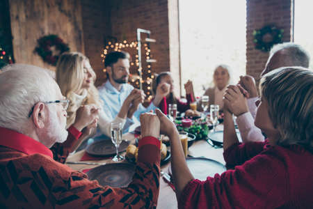 Nice friendly harmony idyllic peaceful calm big full family generation spending wintertime gathering tradition eating lunch holding hands praying in modern industrial loft decorated house indoors