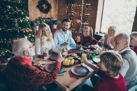 Nice lovely friendly idyllic cheerful cheery big full family spending christmastime day gathering tradition eating brunch drinking in modern industrial loft brick style interior decorated house Stok Fotoğraf