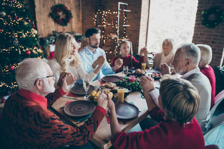 Nice careful affectionate friendly childhood idyllic peaceful calm big full family spending December tradition eating breakfast hold hands pray modern loft brick style interior decorated house Stok Fotoğraf