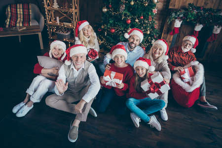 Portrait of nice cheerful cheery big full family brother sister wearing cap hat headwear sitting on floor holding in hands gifts greetings congrats in decorated loft industrial style interior house Stok Fotoğraf